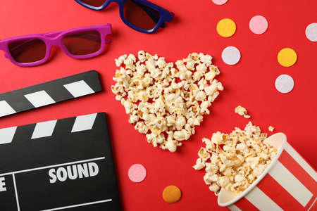 Heart laid out from popcorn, clapperboard, 3d glasses and bucket on red background