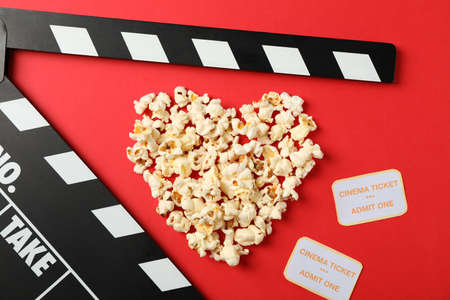 Heart laid out from popcorn, clapperboard and tickets on red background, top view