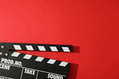 Black clapperboard on red background, space for text Stockfoto