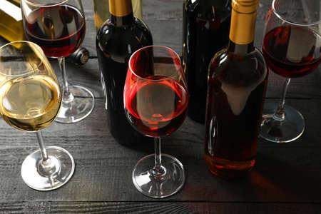 Komposition mit Flaschen und Gläsern verschiedenen Weins auf Holzuntergrund