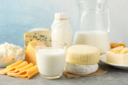 Dairy products on grey table against blue background, copy space