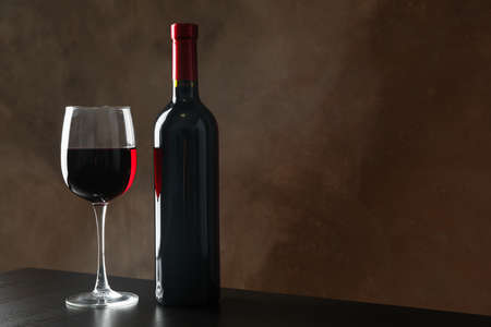 Bottle and glass with wine against brown background, copy space Stock fotó