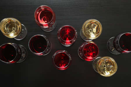 Flat lay. Glasses with different wines on dark background, copy space