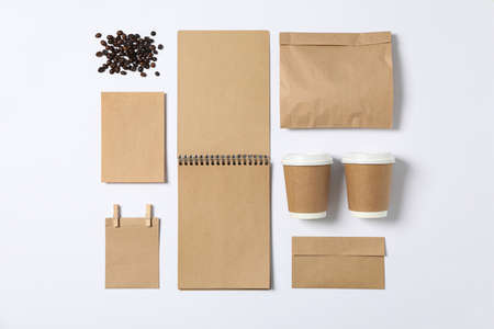 Flat lay. Blank stationery, paper cups and bunch of coffee on white background, mockup