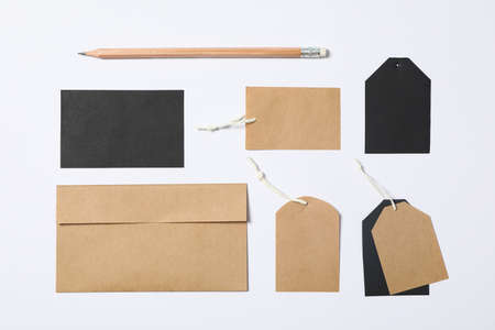 Flat lay composition with envelope, tags and pencil on white background, mockup