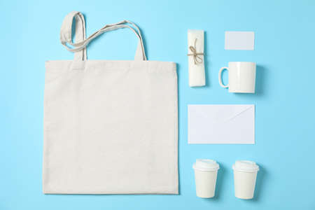 Flat lay composition with cotton bag, paper cups and office supplies on blue background