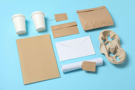 Composition with paper cups and office supplies on blue background, copy space