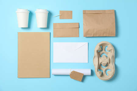 Flat lay. Paper cups and office supplies on blue background, copy space