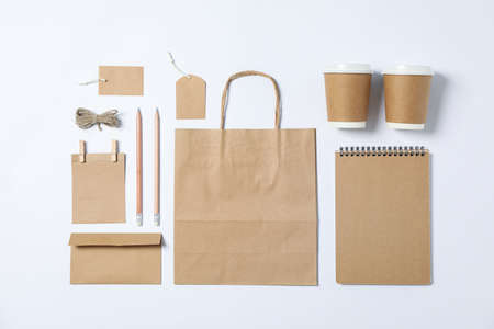 Flat lay composition with blank stationery, paper cups and bag on white background, mockup