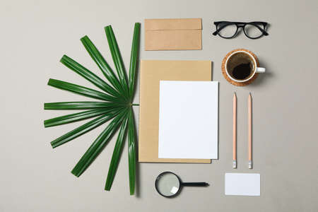 Mockup. Corporate stationery, glasses and palm leaves on grey background. Flat lay