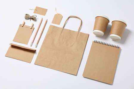 Composition with blank stationery, paper cups and bag on white background, mockup