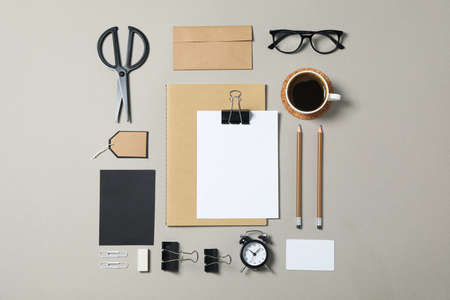 Mockup. Corporate stationery, glasses and alarm clock on grey background. Flat lay
