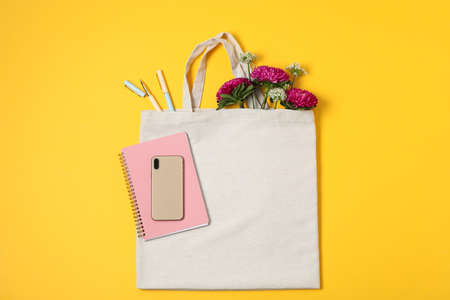 Eco bag, phone, stationery, allium and chrysanthemum on color background, space for text