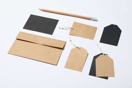 Envelope, tags and pencil on white background, mockup