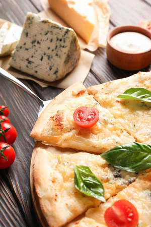 Cheese pizza and ingredients on wooden background, closeup