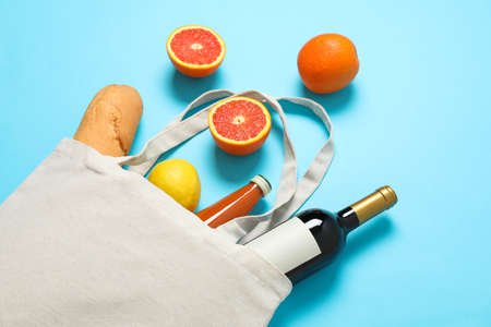 Eco bag with bottle of wine, juice, fruits and baguette on color background, space for text