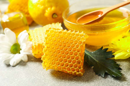 Honeycombs, lemon and flowers on grey background, close up