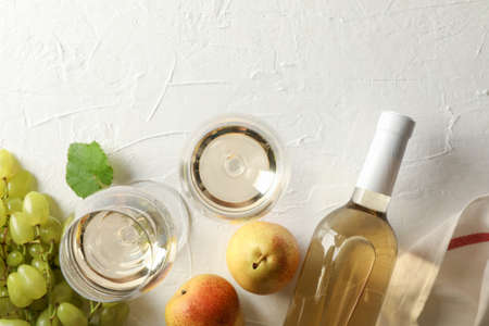 Pears, grape, bottle and glass with wine on white background, top view