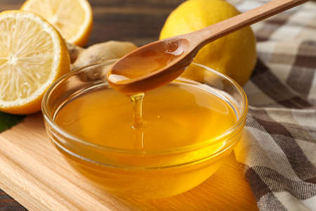Lemons, bowl with honey and dipper on wooden background, close up
