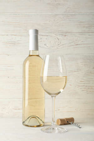 Corkscrew, bottle and glass with wine on white wooden background, copy space