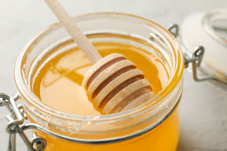 Glass jar with honey and dipper on white background, closeup 版權商用圖片