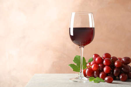 Grape and glass with wine on grey background, space for text