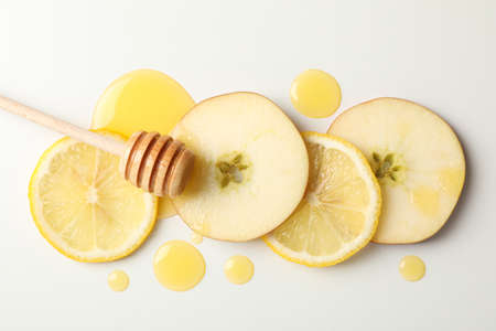 Dipper, honey, apple and lemon slices on white background, top view