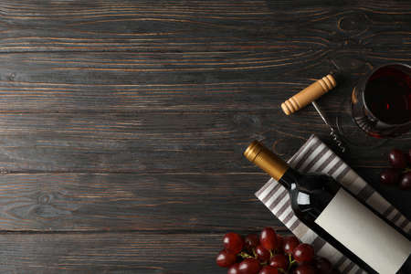 Grape, bottle and glass with wine on wooden background, top view 写真素材