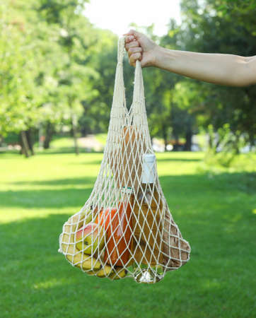 Female hand holding string bag in park, copy space Stock Photo