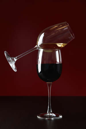 Glasses with wine against red background, copy space