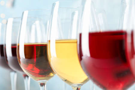 Glasses with wine against light blue background, blurred lights, closeup