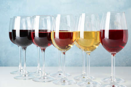 Glasses with different wine on white table against light blue background