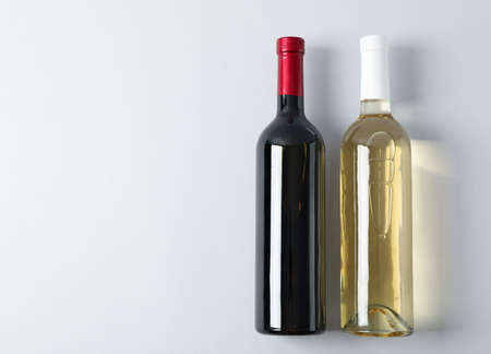 Bottles with wine on grey background, space for text