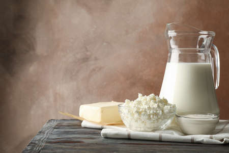Milk, cottage cheese and butter on wooden table against brown background