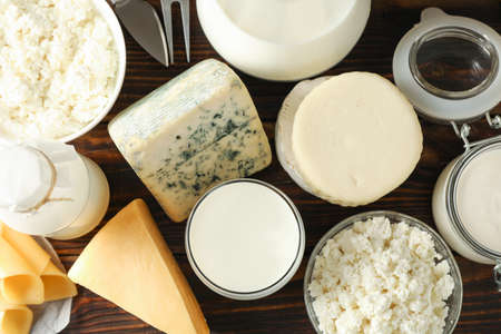 Different dairy products on wooden background, top view