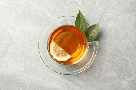 Cup of tea, mint and lemon on grey background, top view