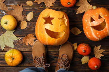 Pumpkins, leaves and legs in boots on wooden background, top view Stock Photo