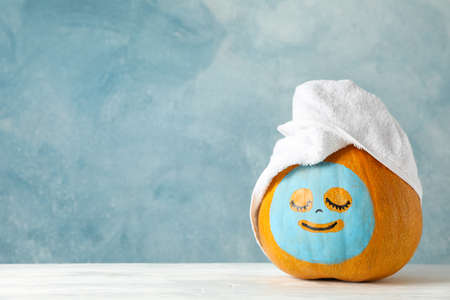 Pumpkin with facial mask and towel on wooden background, copy space 免版税图像