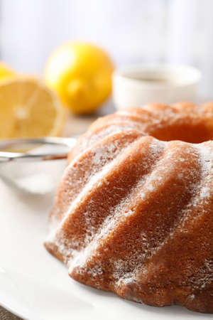 Cake with powder sugar on grey table, close up