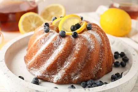 Torta con zucchero a velo e limone su sfondo bianco, primo piano