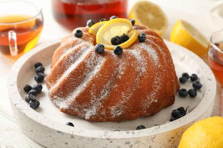Cake with powder sugar and lemon on white background, close up 版權商用圖片 - 130143356