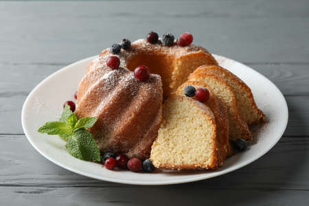 Cake with powdered sugar, berries and mint on wooden background, close up