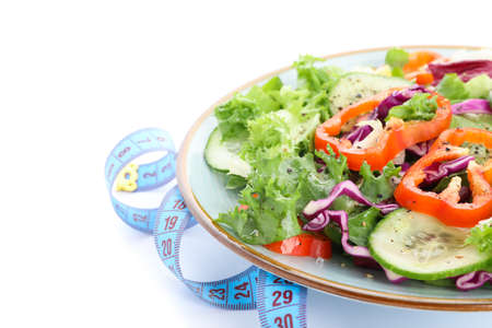 Plate with fresh salad and measuring tape isolated on white background