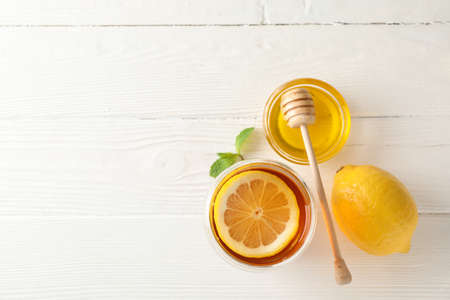 Glass of tea with lemon, mint, honey and dipper on wooden background, top view