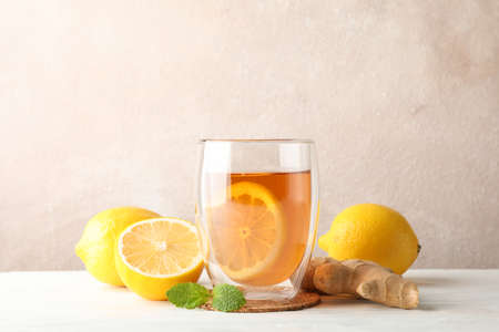 Glass of tea with lemon, mint, honey, dipper and ginger on wooden background ,copy space