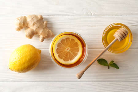 Glass of tea with lemon, mint, honey, dipper and ginger on wooden background, top view