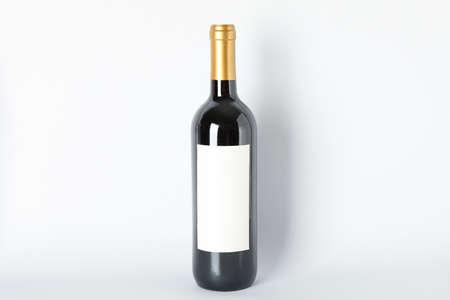 Bottle of red wine on grey background, space for text