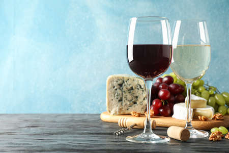 Grape, cheese, corkscrew, glasses with wine, on wooden background, copy space