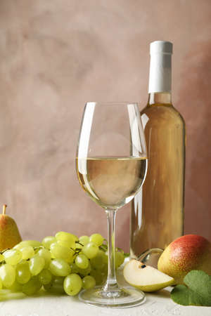 Pears, grape, bottle and glass with wine on white background, copy space