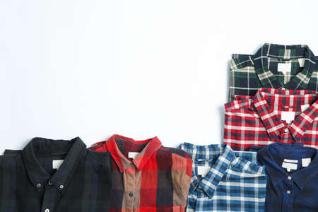 Flat lay with different shirts on white background, copy space